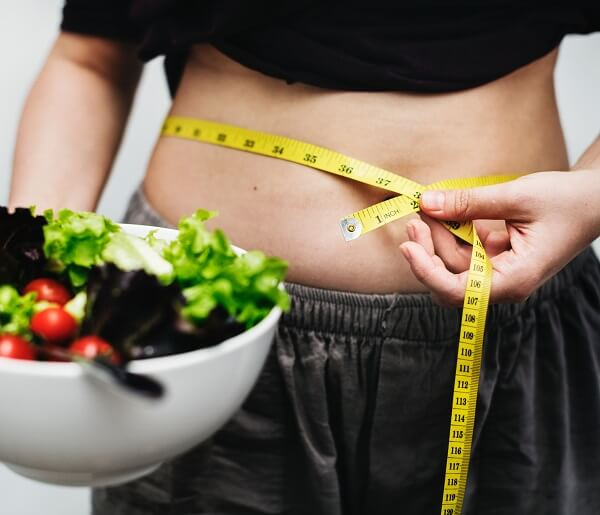 woman with a bowl of salad looking to lose weight