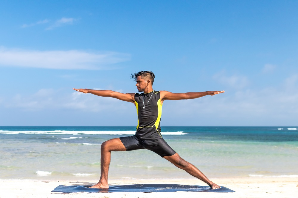 man doing yoga on the beach representing vitamin B9 effects on the mind