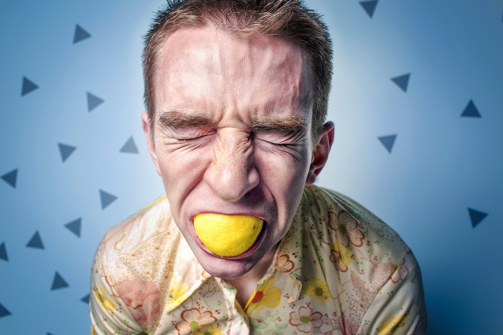 foods that reduce cortisol and adrenaline; a stressed man biting a lemon in anger