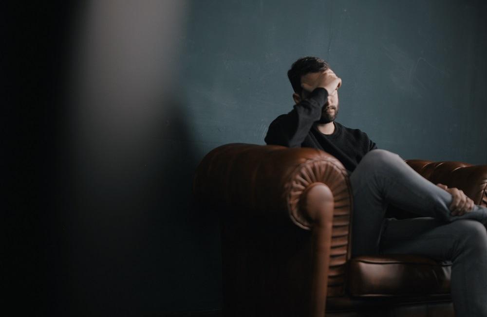 a stressed man sitting on a sofa